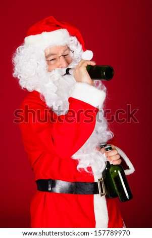 Santa drinking beer over on red background - stock photo