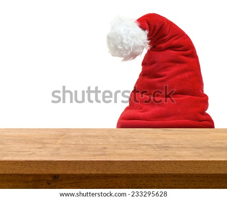 Santa dwarf hiding behind wooden table on white background - stock photo