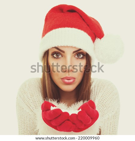 Santa girl blowing snow. Beautiful Caucasian teenage girl wearing red knitted hat and gloves holding and blowing snow. Instant filter. Square format. - stock photo