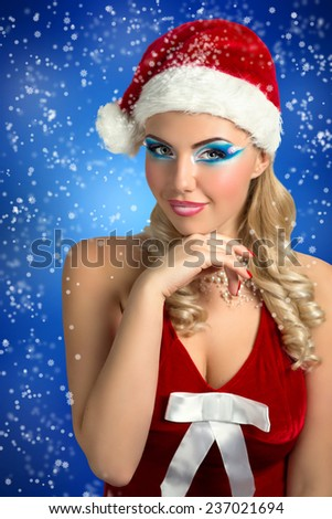 Santa Girl. Card Happy New Year. Santa Claws girl with stylish hair-dress, hat, Christmas New Year party. Pretty curly woman. Close-up portrait, perfect skin, bright professional make-up, pink lips  - stock photo