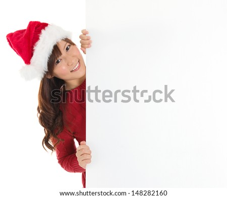 Santa girl peeking from behind blank sign billboard. Advertising photo of young smiling Christmas woman in Santa hat showing paper sign. Asian female model isolated on white background. - stock photo