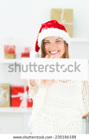 Santa girl peeking from behind blank sign billboard. Advertising photo of young smiling Christmas woman in Santa hat showing paper sign. - stock photo