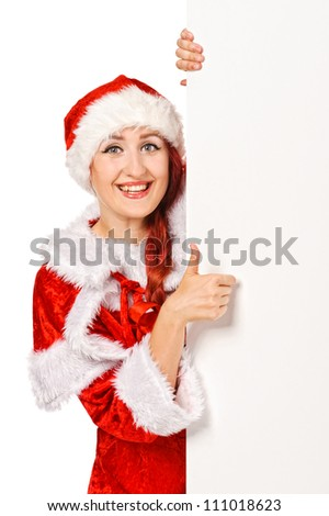 Santa girl peeking from behind blank sign billboard. Caucasian female model isolated on white background