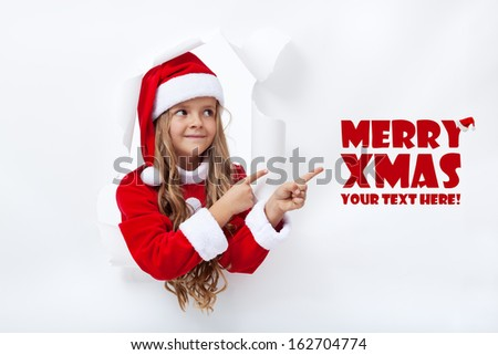 Santa girl pointing to copy space - leaning through hole in paper - stock photo