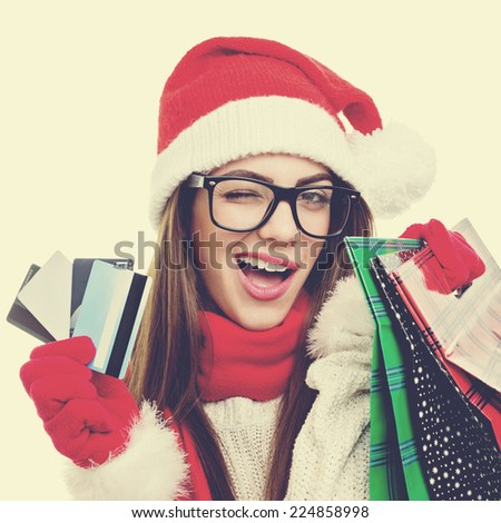 Santa girl with credit cards and shopping bags winking. Christmas woman with hat, scarf and gloves holding credit cards and shopping bags. Square format image with instant filter look. - stock photo