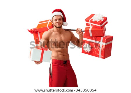 Santa has got a present for you. Muscular handsome Santa Claus with a barbell on his shoulder holding out a gift box - stock photo