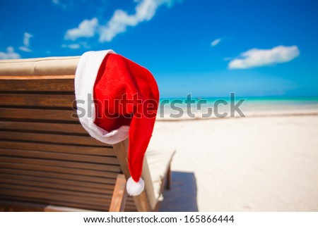 Santa hat on chair longue at tropical caribbean beach - stock photo