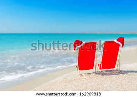 Santa hat on chaise longues at white sand beach against the sea and clear sky - christmas or new year holidays concept - stock photo