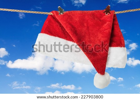 Santa hat on snow against the sky with clouds - stock photo
