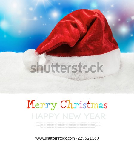 Santa hat on snow on a blue background. The text is presented as a sample and removed - stock photo