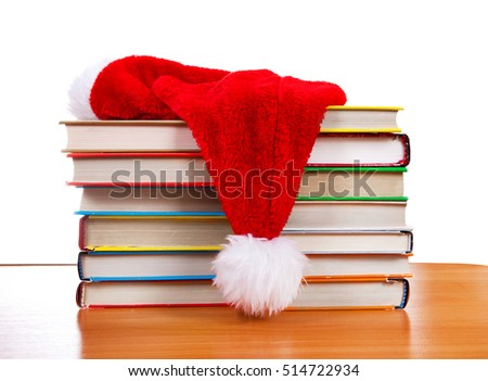 Santa Hat on the Books at the Table on the White Background