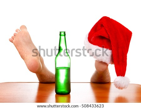 Santa Hat on the Leg and Bottle of a Beer on the Table