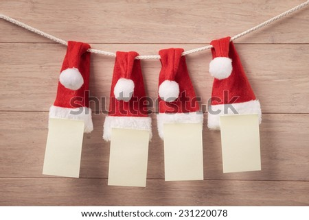 Santa hat on the rope with blank pages against wooden background - stock photo