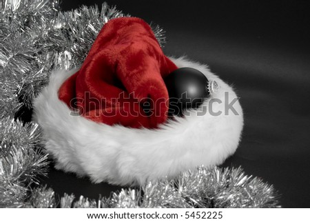 Santa hat with ornament and tinsel on black background
