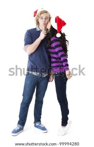 Santa hats and a kiss:  young girl kisses her boyfriend as he sucks on a candy cane - stock photo