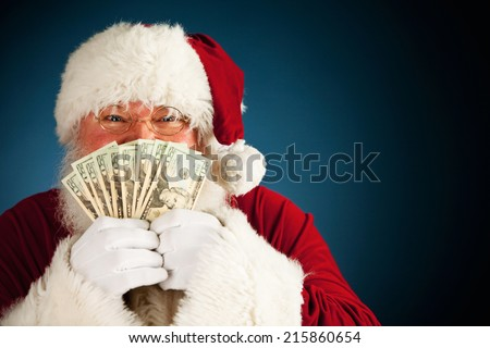 Santa: Holding Up Fanned Out Handful Of Cash - stock photo