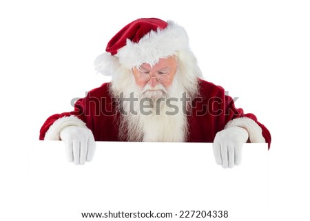 Santa holds a sign and looks down on white background - stock photo