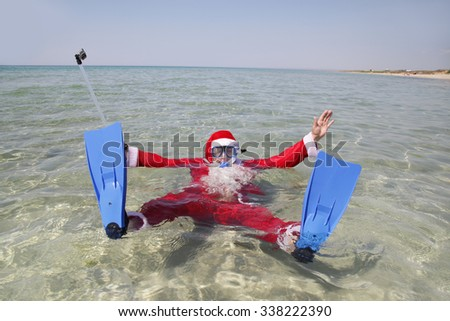 Santa in flippers and mask on resort in clear water - stock photo