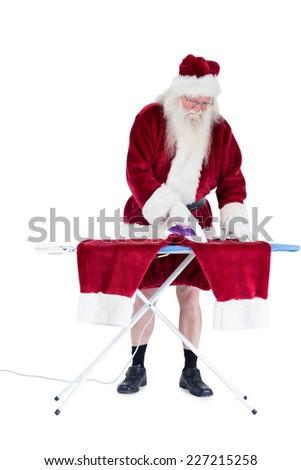 Santa is ironing his pants on white background - stock photo