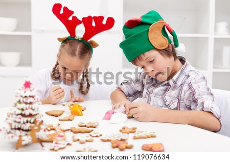 Santa little helpers - reindeer and elf - decorating gingerbread cookies at christmas time - stock photo
