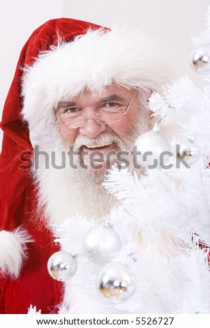 Santa looking out from behind the christmas tree