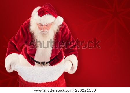 Santa looks in his bag against red background