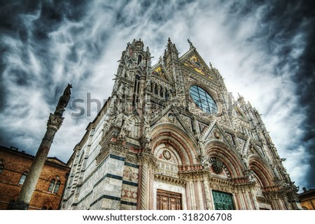 Santa Maria Assunta cathedral in Siena under a dramatic sky. Processed for hdr tone mapping effect - stock photo