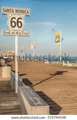 """SANTA MONICA, CA/USA - MAY 14, 2013: """"End of the Trail"""" sign at the Santa Monica Pier, with Pacific Ocean in the background, on Route 66. - stock photo"""