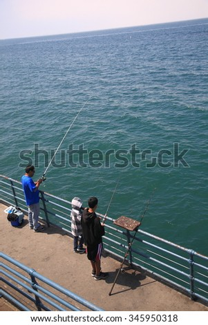 SANTA MONICA, CALIFORNIA - JULY 1: A family fishing on the pier on July 1, 2012 in Santa Monica, California. The city has 3.5 miles of beach locations and averages 340 days of sunshine every year. - stock photo