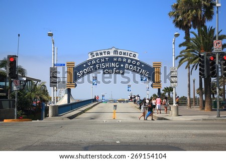 SANTA MONICA, CALIFORNIA - JULY 1: Beach goers at the Santa Monica Pier on Ocean Ave. on July 1, 2012 in Santa Monica, California. The city has 3.5 miles of beaches and 340 days of sunshine a year. - stock photo