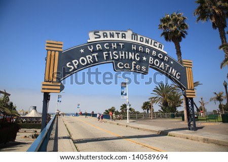 SANTA MONICA, CALIFORNIA - JULY 1: Beach goers stroll under a welcoming arch on July 1, 2012 in Santa Monica, California. The city has 3.5 miles of beach locations and 340 days of sunshine a year. - stock photo