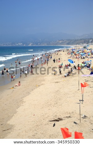 SANTA MONICA, CALIFORNIA - JULY 1: Santa Monica beach-goers on July 1, 2012 in Santa Monica, California. The city has 3.5 miles of beach locations and averages 340 days of sunshine every year. - stock photo