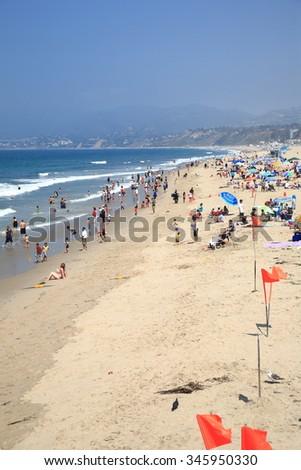 SANTA MONICA, CALIFORNIA - JULY 1: Santa Monica beach-goers on July 1, 2012 in Santa Monica, California. The city has 3.5 miles of beach locations and averages 340 days of sunshine every year. - stock photo