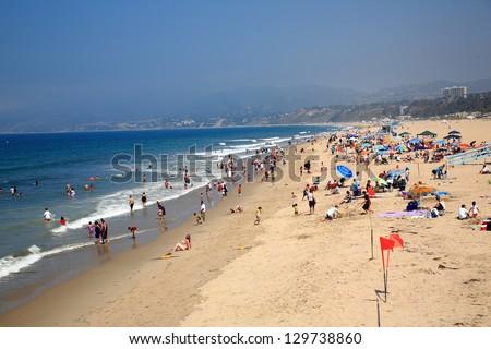 SANTA MONICA, CALIFORNIA - JULY 1: Santa Monica beachgoers on July 1, 2012 in Santa Monica, California. The city has 3.5 miles of beach locations and averages 340 days of sunshine every year. - stock photo