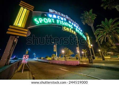 SANTA MONICA - JAN 14, 2015: Famous Santa Monica Sign - Entrance to Santa Monica Pier on Ocean Avenue in LA California at Night with People. Santa Monica is a beachfront city in LA California. - stock photo