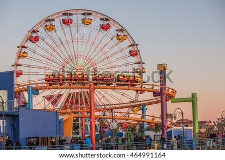 Santa Monica, USA - December 27, 2015: Pacific Park with ferris wheel and roller coaster during sunset