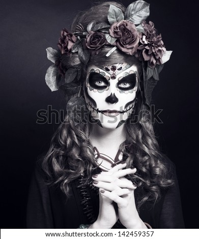 Santa Muerte. Young woman with artistic visage and with roses in her hair/