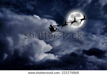 Santa on a sleigh with rein deers over the full moon - stock photo
