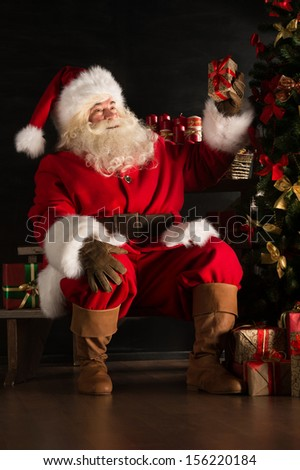 Santa placing gifts under Christmas tree in dark room - stock photo