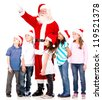 Santa pointing away and showing something to a group of kids - isolated - stock photo