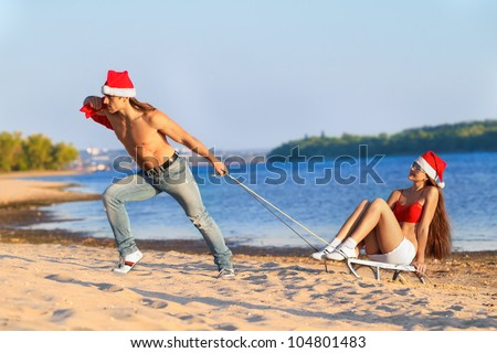 Santa pulling Sexy Santa girl on a sled at the beach.(concept: Tropical winter fun)