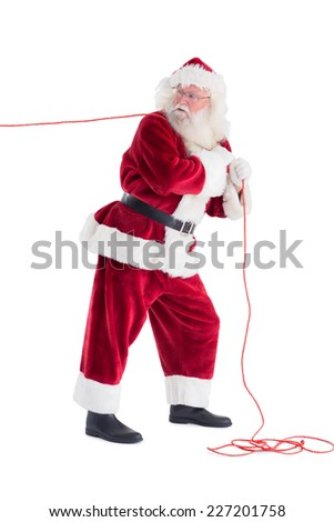 Santa pulls something with a rope and looks back on white background - stock photo