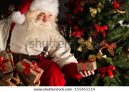 Santa putting gifts under Christmas tree in dark room - stock photo