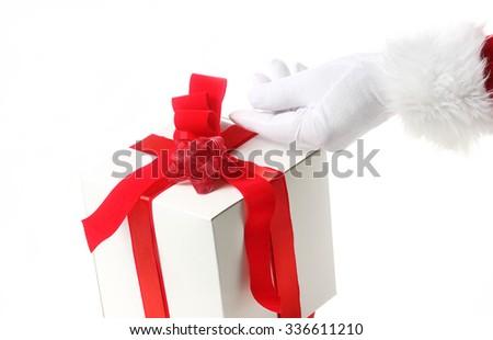 Santa putting the finishing touches on Christmas gift - stock photo