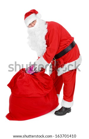 Santa reaches for a gift over white background - stock photo