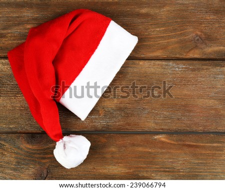 Santa red hat on wooden background - stock photo