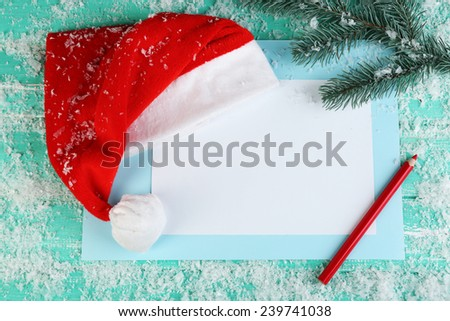 Santa red hat with fir-tree branch, snowflakes, card and pencil on color wooden background - stock photo