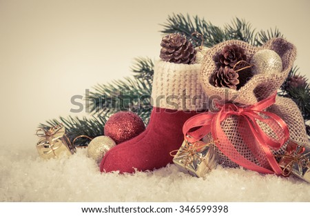 Santa's boot and gift bag on snow. For this photo applied toning in retro style. - stock photo