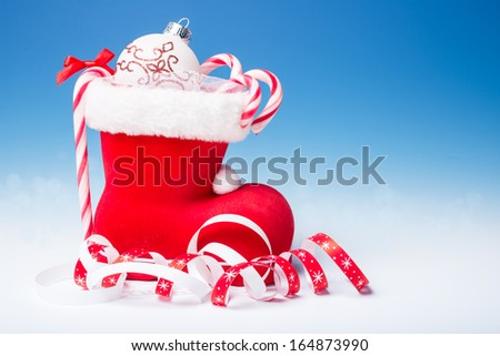 Santa's boot with candy canes and Xmas decorations on blue gradient background, text space  - stock photo
