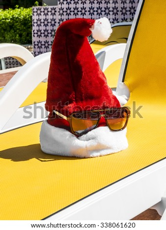 Santa's Cap on a lounger by the pool on a tropical resort in summer day - stock photo
